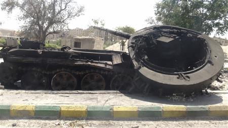 A destroyed Syrian army tank is seen in the Damascus suburb of al-Tel